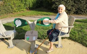"""Une personne âgée fait de l'exercice avec un """"médalier"""", en faisant des moulinets avec les mains"""